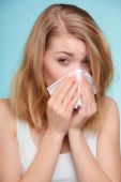 Sick girl sneezing in tissue. — Stock Photo