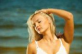 Blonde girl posing on seashore. — Stock Photo