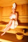 Woman sitting  in wooden sauna — Stock Photo