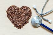 Buckwheat groats heart shaped on wooden surface. — Stock Photo