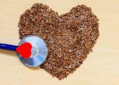 Raw flax seeds heart shaped and stethoscope — Stock Photo