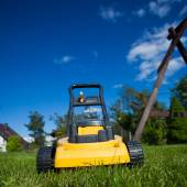 Gardening. Mowing lawn with yellow lawnmower — Stock Photo