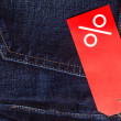 Red label with percent sign on denim — Stock Photo #69499855