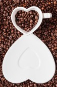 Cup and saucer on coffee beans background — Stock Photo
