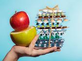 Menschliche Hand halten Stapel von Pillen und Früchten auf blau. — Stockfoto
