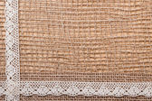 Lace ribbon on burlap cloth — Stockfoto