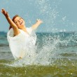 Vacation. Girl splashing water having fun on the sea. — Stock Photo #70447305
