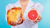Nutritionist holding a cake and fruit — ストック写真