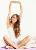 Woman waking up in bed stretching her arms up — Stock Photo