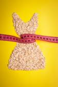 Dress shape made from oatmeal with measuring tape — Stock Photo