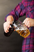 Young man pouring beer from bottle into mug — Stock Photo