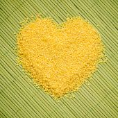 Millet groats heart shaped on green mat surface. — Stock Photo