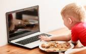 Little boy eating meal while using laptop computer at home — Stok fotoğraf