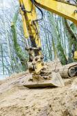 Excavator digging on site in forest environment. — Stock Photo