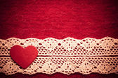 Heart on red cloth background — Stock Photo