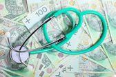 Cost of health care: stethoscope on polish money — Stock Photo