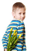Boy hiding bouquet of flowers behind itself — Stock Photo
