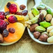 Varieties of dried fruits and nuts on wooden spoons. — Stock Photo #73245083