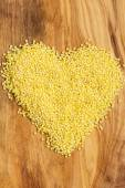 Millet groats heart shaped on wooden surface. — Stock Photo