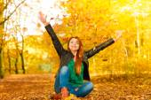 Girl relaxing in autumn park throwing leaves up in the air. — Stock Photo