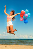 Girl jumping with colorful balloons — Stock Photo
