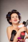 Funny girl styling hair holds many accessories — Stock Photo