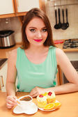 Woman with coffee and cake in kitchen. Gluttony. — Stock Photo