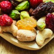Varieties of dried fruits and nuts on wooden spoon. — Stock Photo #74262873