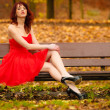 Woman in red dress sitting on bench in autumn park — Stock Photo #74687971