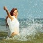 Girl splashing water having fun on the sea. — Stock Photo #74688023