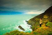 Woman tourist standing on rock cliff — ストック写真