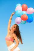 Girl holding balloons sky background — Stock Photo