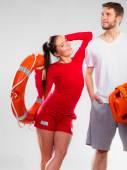 Lifeguard couple holding equipment — Stock Photo