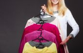 Woman customer holding hangers with clothes — Stock Photo