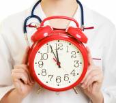Woman doctor holding clock — Stock Photo