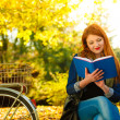 Woman girl relaxing in autumnal park reading book — Stock Photo #77104333