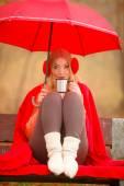 Girl in autumn park enjoying hot drink — Stock Photo