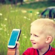 Little boy child playing games on mobile phone outdoor — Stock Photo #77239350