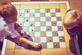Children playing checkers — Stock Photo