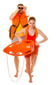Lifeguards in life vest with rescue buoy running — Stock Photo
