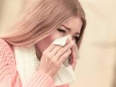 Sick woman  sneezing in tissue. — Stock Photo