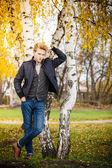 Man posing against autumn birch trees — Stock Photo