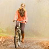 Woman riding bike in autumn park. — Stock Photo
