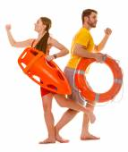 Lifeguards running with rescue ring buoy on duty. — Stock Photo