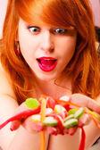 Czerwone włosy kobieta trzymając cukierki w ręce. — Zdjęcie stockowe