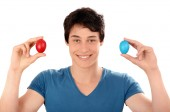 Happy young man holding up red and blue Easter eggs. — Stockfoto