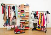 Packing the suitcase for winter vacation. Wardrobe with clothes nicely arranged and a full luggage. — Stock Photo