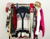 Cute sweaters with snowflakes displayed on a rack. — Stock Photo
