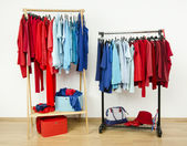 Wardrobe with red and blue clothes hanging on a rack nicely arranged. — Stock Photo