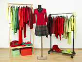 Dressing closet with complementary colors red and green clothes arranged on hangers and a plaid outfit on a mannequin. — Stock Photo